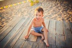 O tema é férias da criança e da praia do verão Um menino caucasiano pequeno senta-se lateralmente em um cais de madeira e admira- imagem de stock royalty free