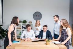 O tema é negócio e trabalhos de equipe Um grupo de trabalhadores de escritório caucasianos novos dos povos que realizam uma reuni fotografia de stock