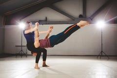 O tema de Acroyoga e de poses da ioga Praticar de Acroyogis com o luminoso do estúdio A base da mulher mantém o inseto do homem n Imagens de Stock Royalty Free
