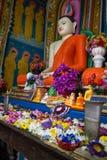 O templo Kandy-Vihara Flores perto da estátua do insid da Buda Imagens de Stock