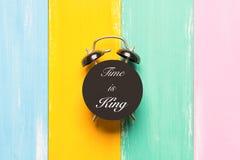 O tempo é rei que o despertador preto nos fundos coloridos com tempo de fraseio é rei Fotografia de Stock Royalty Free