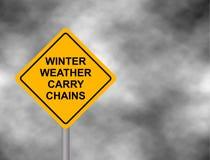 O tempo do inverno leva as correntes que advertem o sinal de estrada Sinal de aviso amarelo do perigo, em um aviso cinzento do ma ilustração royalty free