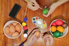 O tempo feliz da família dos membros está pintando ovos coloridos com uma escova de pintura para prepara o dia da Páscoa foto de stock