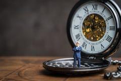O tempo prova para o conceito do sucesso comercial, líder diminuto dos povos imagens de stock