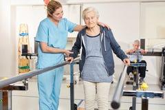 O terapeuta apoia a mulher superior na escada rolante foto de stock