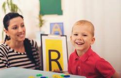 O terapeuta de discurso ensina os meninos dizer a letra Fotos de Stock