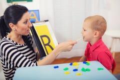 O terapeuta de discurso ensina os meninos dizer a letra R Foto de Stock Royalty Free