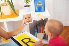 O terapeuta de discurso ensina os meninos dizer a letra R Imagens de Stock Royalty Free