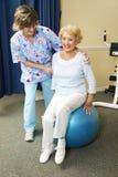 O terapeuta físico trabalha com sénior Foto de Stock Royalty Free