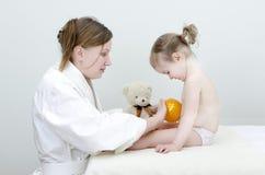 O terapeuta faz uma massagem da criança Imagens de Stock Royalty Free