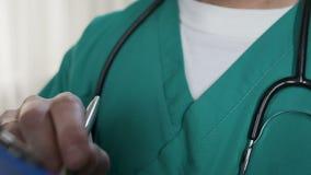 O terapeuta masculino que enchem o formulário médico e o paciente de escuta, close-up dispararam da mão vídeos de arquivo