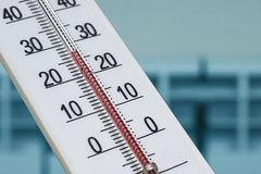 O termômetro branco da sala do álcool mostra uma temperatura confortável na casa na perspectiva de um radiador de aquecimento fotografia de stock royalty free