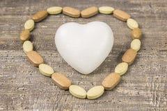 O termômetro de vidro, medicamentações do coração marca a tabela de madeira do fundo A vista da parte superior Fotografia de Stock Royalty Free
