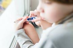 O termômetro do menino da criança mede a temperatura fotografia de stock