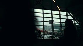 O terminal de aeroporto, pessoa mostra em silhueta o passeio perto contra uma janela de vidro filme
