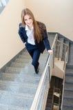 O terno do homem vestindo novo da mulher de negócio que anda em escadas Imagens de Stock Royalty Free
