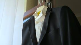 O terno do noivo que pendura em uma janela vídeos de arquivo