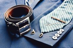 O terno dos homens clássicos da forma com a correia de couro preta, o laço azul listrado, ufflinks dourados e grampo de laço Home imagem de stock royalty free