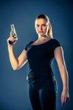 O terrorista perigoso da mulher vestiu-se no preto com uma arma em seu han imagem de stock
