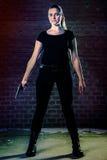 O terrorista perigoso da mulher vestiu-se no preto com uma arma em seu han Foto de Stock
