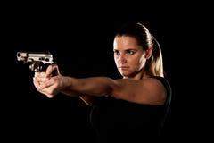 O terrorista perigoso da mulher vestiu-se no preto com uma arma em seu han fotografia de stock