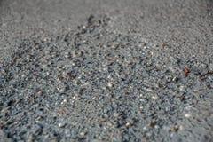 O teste padrão cinzento do asfalt nas pedras pequenas da cidade incluiu o close up detalhado foto de stock