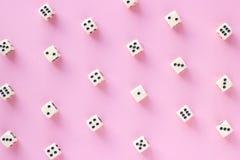 O teste padrão dos dados do jogo no fundo cor-de-rosa no plano coloca o estilo Imagens de Stock