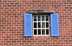 O teste padrão e o ferro da parede de tijolo ancoram a placa em uma construção velha Imagem de Stock