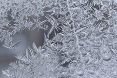O teste padrão gelado branco do close-up com muitos água congelada deixa cair na janela do inverno como o fundo foto de stock