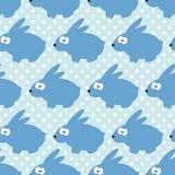 O teste padrão sem emenda com coelhos no azul pontilhou o fundo Imagens de Stock Royalty Free