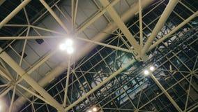 O teto de locais de um salão enorme ou de fábrica No metal cultiva projetores fixos filme