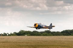 O Texan AT-6 voa baixo sobre a pista de decolagem Fotografia de Stock