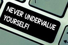 O texto da escrita nunca desvaloriza-se Conceito que significa certamente não subestimar sua intenção real da chave de teclado do foto de stock royalty free
