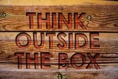 O texto da escrita pensa fora da caixa O significado do conceito que pensa da solução nova e criativa conduz ao fundo de madeira  foto de stock royalty free