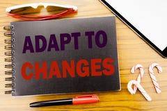 O texto do anúncio da escrita adapta-se às mudanças Conceito do negócio para o futuro novo da adaptação escrito no livro do cader fotografia de stock royalty free