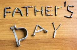 O texto do dia de pai é apresentado de um grupo de chaves de fenda e de parafusos em uma tabela de madeira fotos de stock