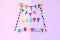 O texto do feliz aniversario com papel colorido embandeira a festão imagens de stock