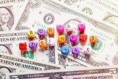O texto do orçamento, do negócio e do imposto das palavras em cubos de madeira coloridos em cédulas americanas do dólar Conceitos imagem de stock royalty free