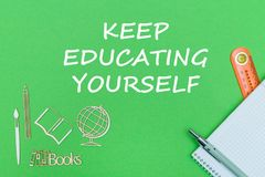 O texto mantém-se educar-se, miniaturas de madeira das fontes de escola, caderno no fundo verde imagem de stock royalty free