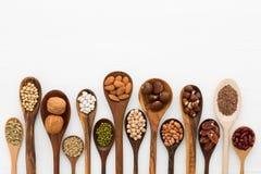O tipo diferente dos feijões e as lentilhas na colher de madeira no branco cortejam foto de stock royalty free