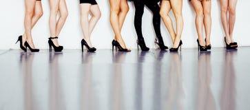 O tipo diverso par de pés da mulher na altura coloca saltos as sapatas pretas isoladas no fundo e no assoalho brancos, pessoa da  Fotografia de Stock Royalty Free