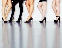 O tipo diverso par de pés da mulher na altura coloca saltos as sapatas pretas isoladas no fundo e no assoalho brancos, pessoa da  Foto de Stock Royalty Free