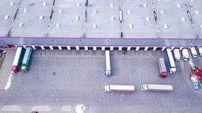 O tiro aéreo da doca de carga industrial do armazém onde muitos transportam com semi reboques carrega a mercadoria aéreo fotografia de stock