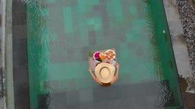 O tiro aéreo de um turista da jovem mulher tem seu próprio café da manhã pessoal em uma tabela de flutuação em uma piscina privad vídeos de arquivo