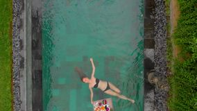 O tiro aéreo de um turista da jovem mulher tem seu próprio café da manhã pessoal em uma tabela de flutuação em uma piscina privad filme