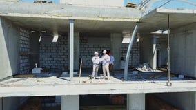 O tiro aéreo dos construtores team no canteiro de obras que discutem o plano do projeto com a utilização do arquiteto e do contra video estoque