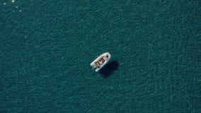 O tiro aéreo dos pares felizes que relaxam e que tomam sol em um barco estacionou no meio da água mediterrânea a mais limpa video estoque