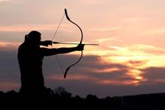 O tiro ao arco da silhueta dispara em uma curva em um alvo no céu do por do sol Imagens de Stock Royalty Free