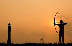 O tiro ao arco da silhueta dispara em uma curva em uma maçã na madeira Foto de Stock Royalty Free