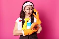 O tiro ascendente próximo da empregada doméstica bonita veste a faixa, a camisa branca de t, o avental marrom e as luvas de borra fotos de stock